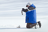 Middletown, New York - A man unhooks a fish he caught while ice fishing at the Shawangunk Fish and Game Association pond during the association's annual contest on Feb. 8, 2014. ©Tom Bushey / The Image Works
