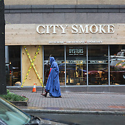 Charlotte, NC- September 22, 2016: A man draped in robes carrying a staff walks by City Smoke, a restrurant damaged in the protest the evening before. CREDIT: LOGAN R CYRUS FOR THE NEW YORK TIMES