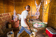16 JUNE 2012 - GILA RIVER INDIAN COMMUNITY, PHOENIX, AZ: Ibrahim Swara-Dahab walks through the killing room on his goat farm. Swara-Dahab, 57, left Somalia in 1993. He lived in a refugee camp in Kenya for five years before coming to the United States and settled in the Phoenix area in 2006. He got a $10,000 loan from the micro-enterprise development program for refugees. The money allowed him to buy dozens of goats and sheep, each worth $130 to $200, turning his one-sheep operation into a money-making, time-consuming herd. He now operates a full time goat ranch and slaughter house. He slaughters his goats and sheep in the Muslim halal tradition. Most of his customers are fellow refugees and Muslims who prize goat meat or eat only meat slaughtered according to halal traditions. His butchering operation is on the Gila River Indian Community, near Laveen, AZ, just southwest of Phoenix.    PHOTO BY JACK KURTZ