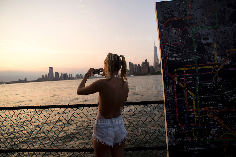 July 12, 2014 - New York, NY : Concertgoer Natalie Haschek snaps a photo of the New York City and Jersey City skylines at sunset as she attends the Hyte Park Festival -- an electronic dance music festival -- on Governor's island, on Saturday evening.  The 172-acre island, which served for nearly two centuries as a military installation, was taken over by the City and State of New York (152 acres), and the National Park Service (22 acres), in 2003. CREDIT: Karsten Moran for The New York Times