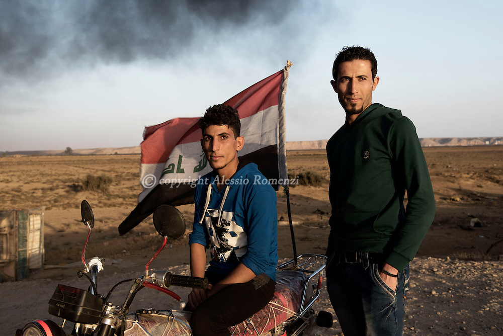 Iraq, Qayyara: Inhabitants of Qayyara pose for a portrait at the northern entrance of the city where is visible the smoke of the crude oil fields that IS fighters set on fire as they retreated from the city. Alessio Romenzi