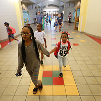 April Evans holds the hand of her daughter, Makylie Thompson, as they walk into the first grade hallway on the first day back to school at Saltillo Primary School on Thursday morning.
