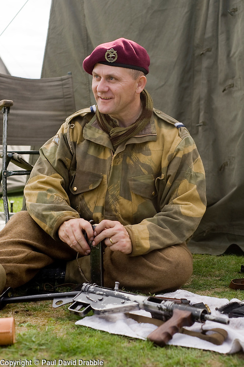 Re-enactor portrays a member of the 22nd Independent Parachute company loads a magazine for his Sten sub machine gun.  Note the cap badge is Army Air Corps with kings crown and eagle facing right and not the usual Kings Crown Parachute Regiment Cap Badge which the company would have worn later in the war. Battle of Britain Celebration at Lytham 1940s War Weekend 21 Aug 2010 .Images © Paul David Drabble..