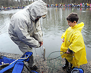 From left, Gene Arico pulls a fish in for Braydeom Arico, 5, of Plumstead, on the first day of trout season at Fanny Chapman Pond Saturday April 2, 2016 in Doylestown, Pennsylvania.  (Photo by William Thomas Cain)
