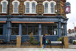 © Licensed to London News Pictures. 08/06/2020. London, UK. A woman walks past 'The Westbury' pub in north London. It has been reported that pubs and restaurants in England could reopen on 22 June to serve customers outdoors. Photo credit: Dinendra Haria/LNP