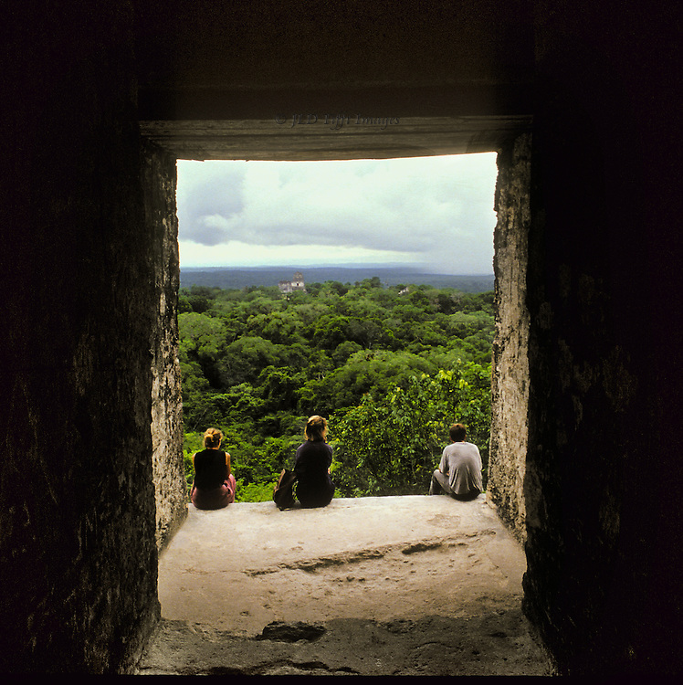 Tikal: view of the forest from the top of the Temple I or II.  Three sightseers seated on the top step just outside the doorway opening.  Another temple shows its top above the treetops in the distance.  Cloudy sky.