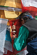 China, Tibet, Lhasa, Detail of Tibetan Buddhist prayer flags and , a local Tibetan woman is praying with her head against some Tibetan Buddhist prayer flags. She is holding a prayer wheel in her hand.