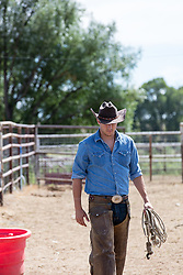 cowboy walking on a ranch with a lasso