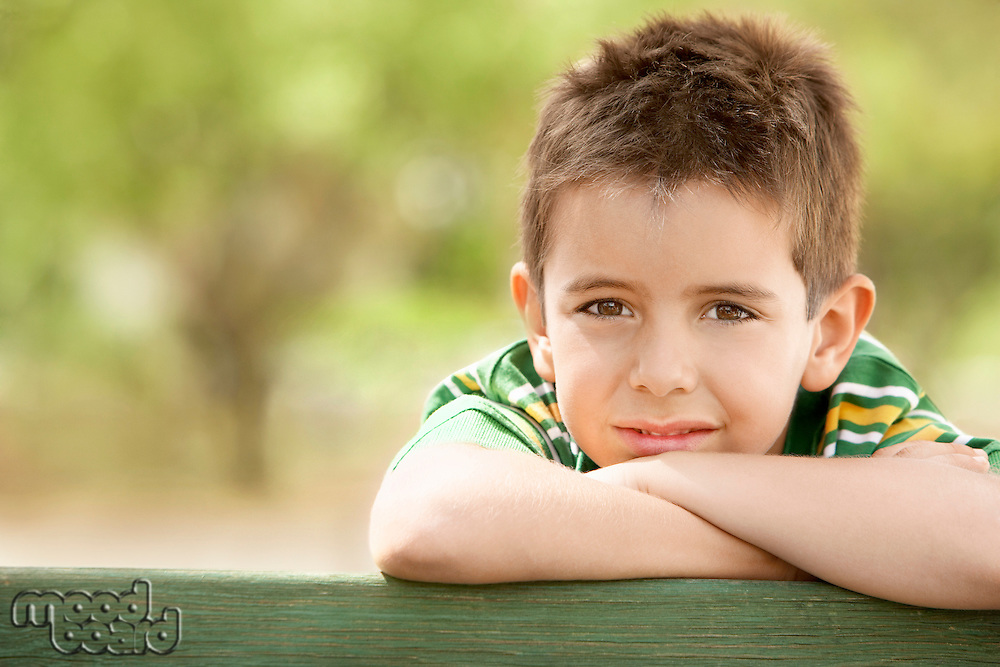 Boy (7-9) leaning against railing front view portrait.