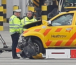 © Licensed to London News Pictures. 14/02/2018. London, UK. Damage to the front of the vehicle (left, next to police officers). Police and airport vehicles are seen in the tarmac at Heathrow Airport after this morning's incident near T5.Photo credit: Peter Macdiarmid/LNP