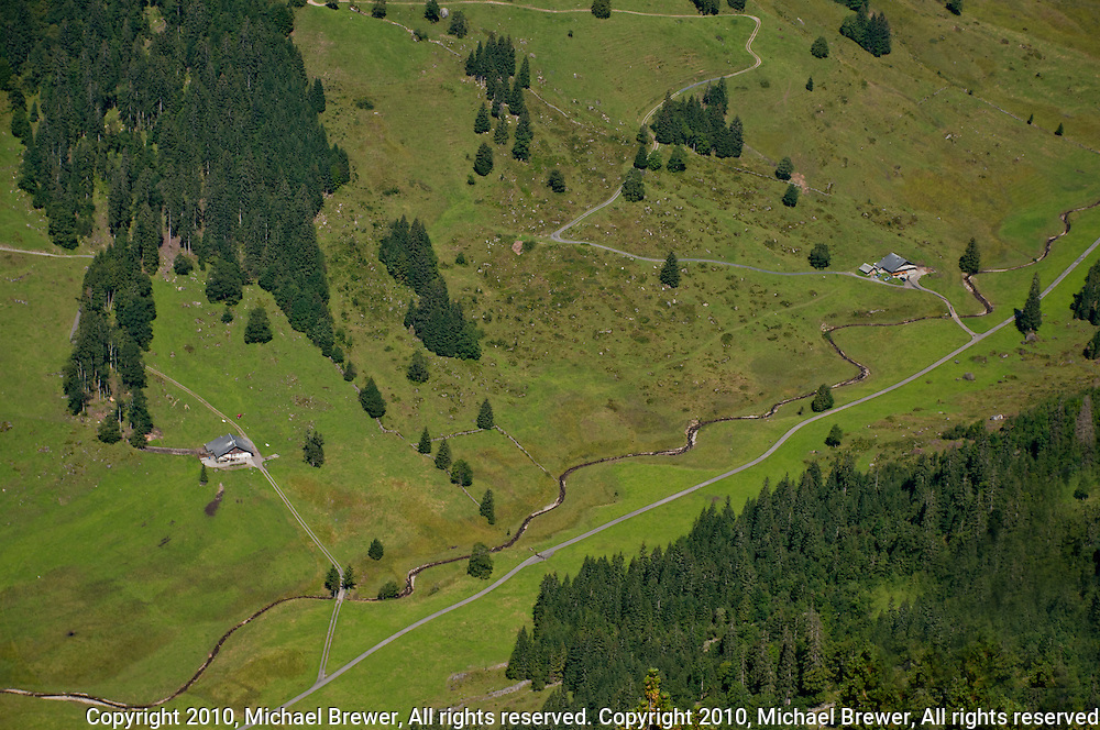 Looking down at farm houses down in the valley from the Niederhorn in the Swiss Alps Berner Oberland, Switzerland.