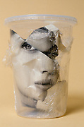 magazine photo of face of a woman in a plastic jar