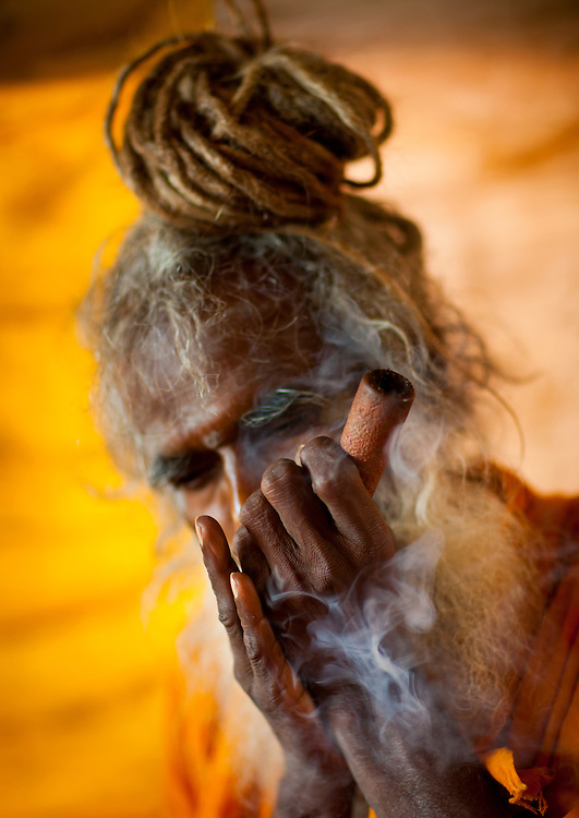 A Naga Sadhu smoking pot during Maha Kumbh Mela, a festival known as world's largest congregation of religious pilgrims. Allahabad, India.