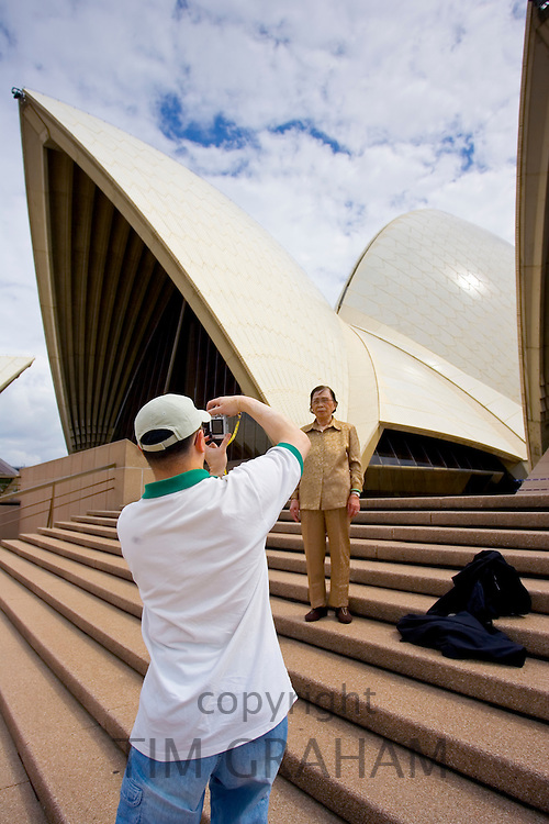Tourists take photographs outside Sydney Opera House, Australia