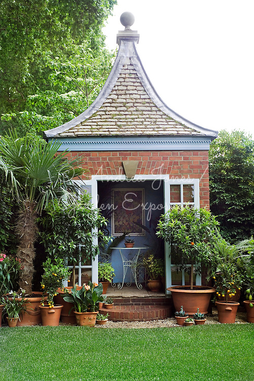 'The Chris Beardshaw Garden'. Design by Chris Beardshaw for  RHS Chelsea 2007 Silver-Gilt Medal. Based on Hidcote. Summer house/pavilion with steps & french windows. Terracotta pots with Canna sp, Citrus trees, palm, succulents, Agapanthus sp & ferns.