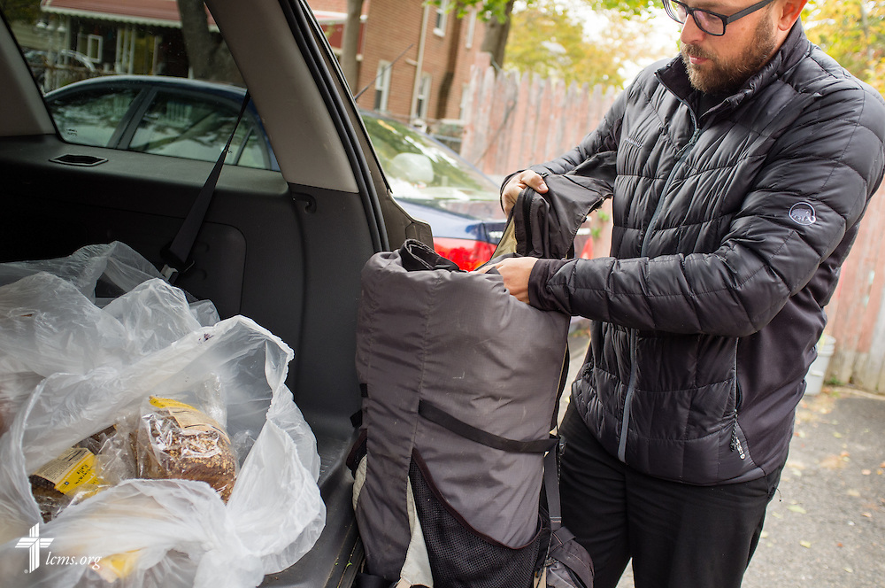 The Rev. Adam DeGroot, new national missionary and pastor at Shepherd of the City Lutheran Church, a church plant and focus of Philadelphia Lutheran Ministries, loads food to distribute into his bag on Monday, Nov. 2, 2015, in Philadelphia.  LCMS Communications/Erik M. Lunsford