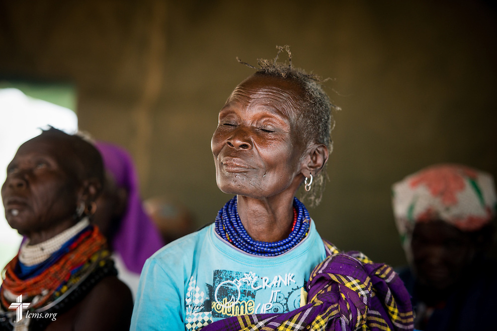 A patient smiles and closes her eyes as the Rev. Robert Pase, pastor of Grace Lutheran Church, Midland, Texas, and Faith Lutheran Church, Andrews, Texas, evangelizes alongside a local member of Lutheran Hour Ministries during a LCMS Mercy Medical Team clinic on Monday, June 20, 2016, in Nataparkakono, a village in Turkana, Kenya.  LCMS Communications/Erik M. Lunsford