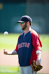 OAKLAND, CA - JUNE 22:  Dustin Pedroia #15 of the Boston Red Sox tosses a baseball during batting practice before the game against the Oakland Athletics at O.co Coliseum on June 22, 2014 in Oakland, California. The Boston Red Sox defeated the Oakland Athletics 7-6 in 10 innings.  (Photo by Jason O. Watson/Getty Images) *** Local Caption *** Dustin Pedroia