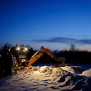 Chad Henry using a backhoe to load his truck with sand as he and his brother, Johnathan Beauchamp and a couple of colleagues prepare to sand the roads to provide traction for vehicles during snowy and icy conditions at the Ochiichagwe'Babigo'Ining Ojibway Nation reserve (also known as the Dalles First Nation) in Northern Ontario, Canada on 14 December 2016.