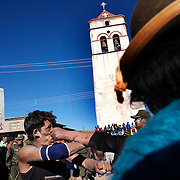 Police watch over one on one fighting between rival villagers in the streets of Macha during the Tinku Festival. Macha, Bolivia, 4th May 2010, Photo Tim Clayton ...Each May, up to 3000 thousands indigenous Bolivian indians descend on the isolated mountainous village of Macha 75 miles north of Potosi in the Bolivian Andes. The 600 year old pre-hispanic Bolivia Festival of Tinku sees villagers from all over the region march into town to be pitted against each other in a toe to toe fist to fist combat.. They dance and sing in traditional costume and drink 96% proof alcohol along with chicha, a fermented beverage made from corn. Townspeople and sometimes the police oversee proceedings who often use tear gas to try and control the villages, whipped into a fighting frenzy by the dancing and alcohol, but as the fiesta goes on things often escalate beyond their control, with pitched battles between rival villages break out,  The blood spilt is an offering to the earth goddess - Pachamama - to ensure a good harvest for the coming year. Over the years dozens have died, yet the rite continues.