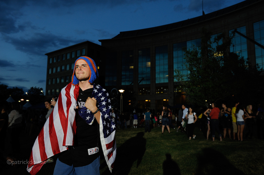 "Aurora, CO: Chris Gibson, 24, of Aurora is wrapped in the US flag in the waning light after the large vigil for the theatre shooting victims. He said, ""I just am thankful for all the heroes and wanted to pay my respects to the victims."" He said he was friends with and knew both dead victims Veronica Moser-Sullivan and Micayla Medek and some of the wounded."