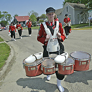 After marching over 4 miles in the annual Tulip Festival Parade wearing wooden shoes, this drummer with the MOC Floyd Valley marching band from Orange City, Ia., quickly sheds the shoes for the comfort of stocking feet.  The NW Iowa town has a proud Dutch heritage, and keeps many traditions alive during their annual festival.