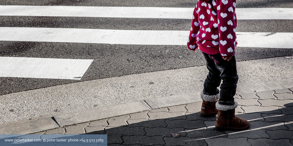 Child in red sweater with white hearts, standing beside a pedestrian crossing, Osaka, Japan.