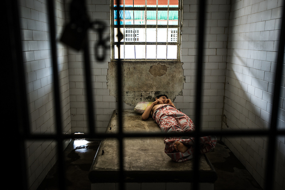 BARQUISIMETO, VENEZUELA - JULY 28, 2016: Jusmar Torres while upset in solitary confinement, naked except for a blanket. She had been in the isolation cell against her will for the past four days because her medication for a mood disorder and depression ran out two weeks ago. She was naked because hospital staff had stripped her of her clothes which they feared she would use to hang herself. She had already constructed a noose out of a bed sheet the week before they locked her up. This day, she was missing 4 of the 5 medications prescribed to her to manage her disorder. The nursing staff said she has to be locked up because she becomes very violent when she is unmedicated - however they also said that she is completely different when she has all of her medicines - that she is kind and helpful, and that they can even give her the keys to the women's ward and be trusted with responsibilities like letting people in and out of the locked gates. PHOTO: Meridith Kohut