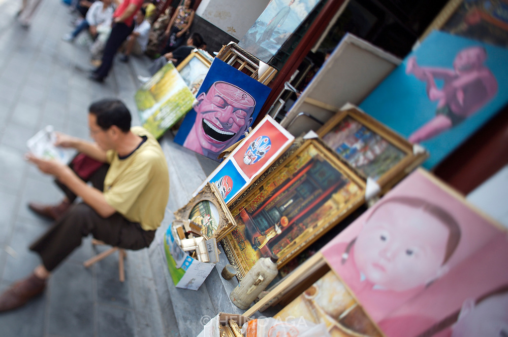 Panjiayuan weekend market. Shop selling copies of modern art by famous Chinese artists.