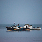 Two wooden fishing boats anchored in clam waters off Panama City, Panama, on Panama Bay.