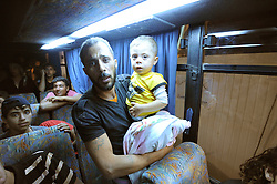 Syrian refugees at the Zaatari refugee camp in Jordan. Abu Mohammad Ammari with 4 year old son Mohammad aboard a coach to return to Daraa in Syria, September 3, 2012. Photo by Nick Cornish/i-Images.