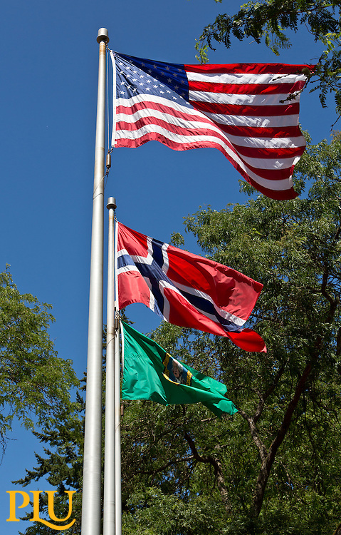 The flags of the United States, Norway and the State of Washington billow in the breeze above Red Square at PLU on Monday, July 20, 2015. (Photo: John Froschauer/PLU)