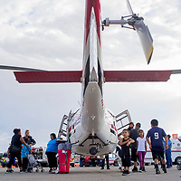 Children and their families line up to see the Tristate Care Flight helicopter during the National Night Out event at the Rio West Mall in Gallup Tuesday.