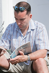 Man with hearing impairment studying book.
