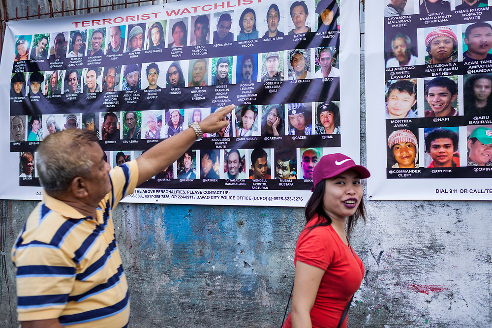 Davao City, Mindanao, Philippines - JUNE 18: Visitors examine two large posters of Wanted Terrorist posted at the Roxas Night Market.  Roxas Night Market was bombed on September 16, 2016.  14 people were killed and 70 were injured and three men who are linked to the Maute Group were arrested for the bombing.