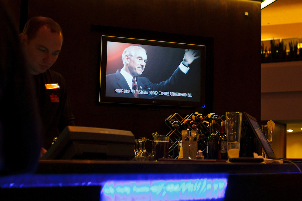 Bartender Nicholas Gunsolley places an order while a Ron Paul advertisement flashes on screen during a football game commercial break  at the City Center Lounge leading up to the Iowa Caucuses on Sunday, January 1, 2012 in Des Moines, Iowa.