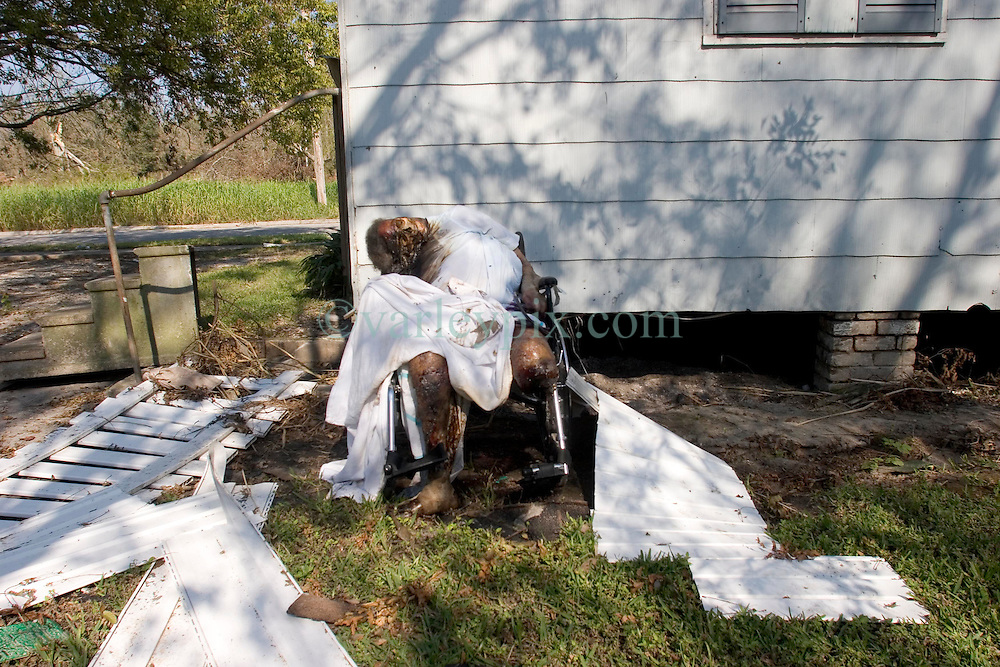 08 Sept 2005. New Orleans, Louisiana.  Hurricane Katrina aftermath. <br /> An old lady rots in her wheelchair, dumped behind a dentist office in East New Orleans. Her body has been there for 10 days.<br /> Photo; ©Charlie Varley/varleypix.com