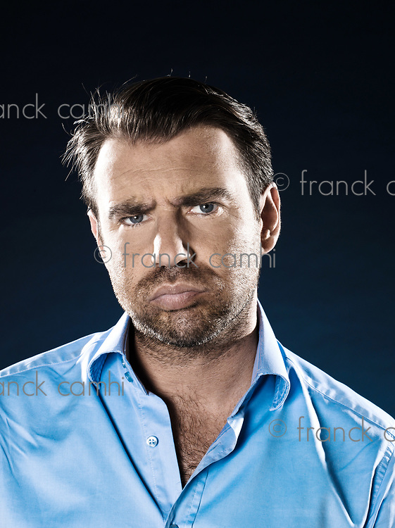 caucasian man unshaven frown bored portrait isolated studio on black background