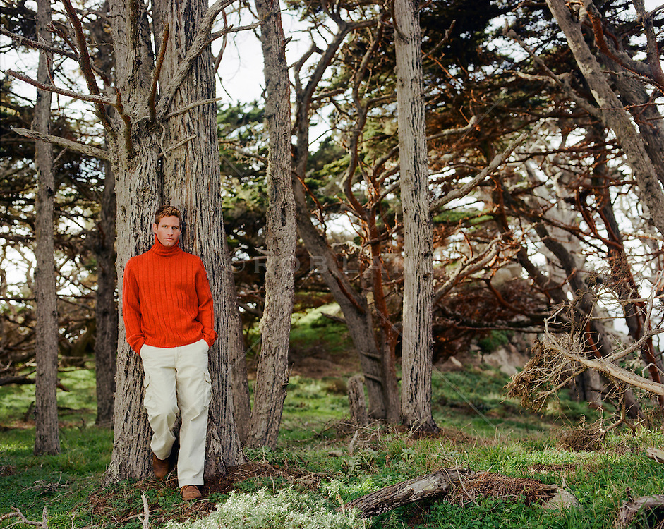 All American man wearing a colorful turtleneck sweater in the woods of Northern California