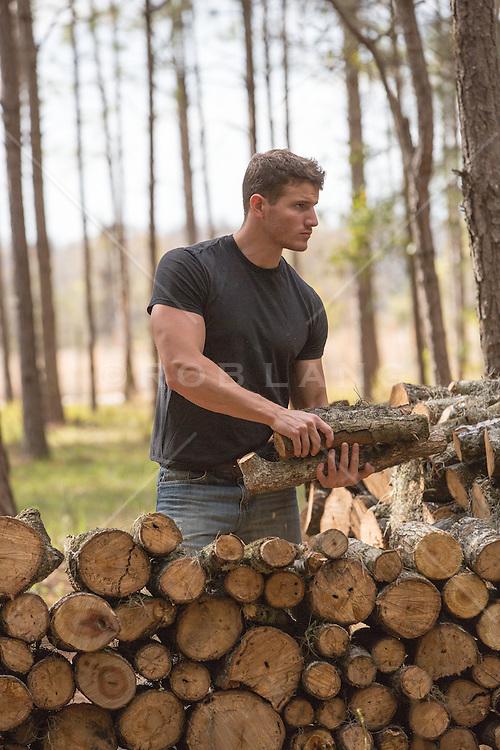 muscular man piling up firewood
