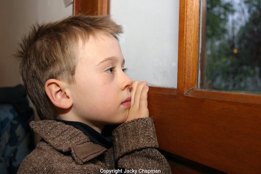 Young child peeking out the front door