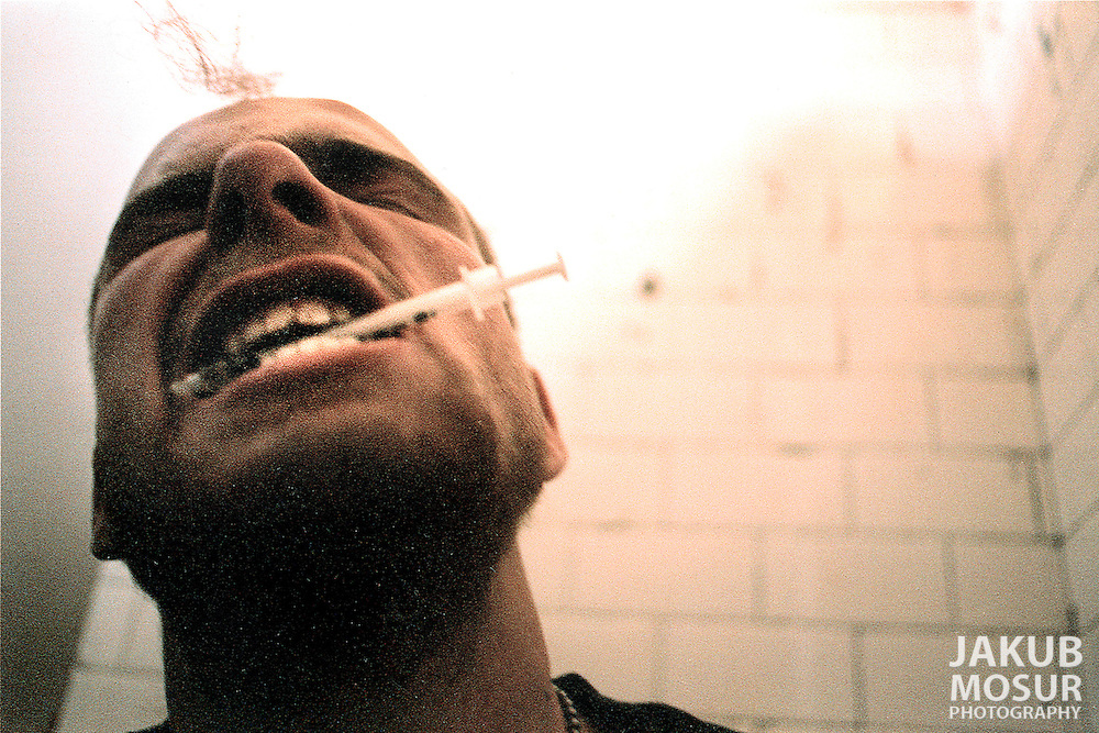 Beavis, real name Aaron Lee, holds a syringe in his mouth right after he shot up heroin at a public restroom in the Panhandle in San Francisco in April 1998. Beavis, 20, is a runaway living in the Haight-Ashbury neighborhood of San Francisco for the past five years. Photo by Jakub Mosur.
