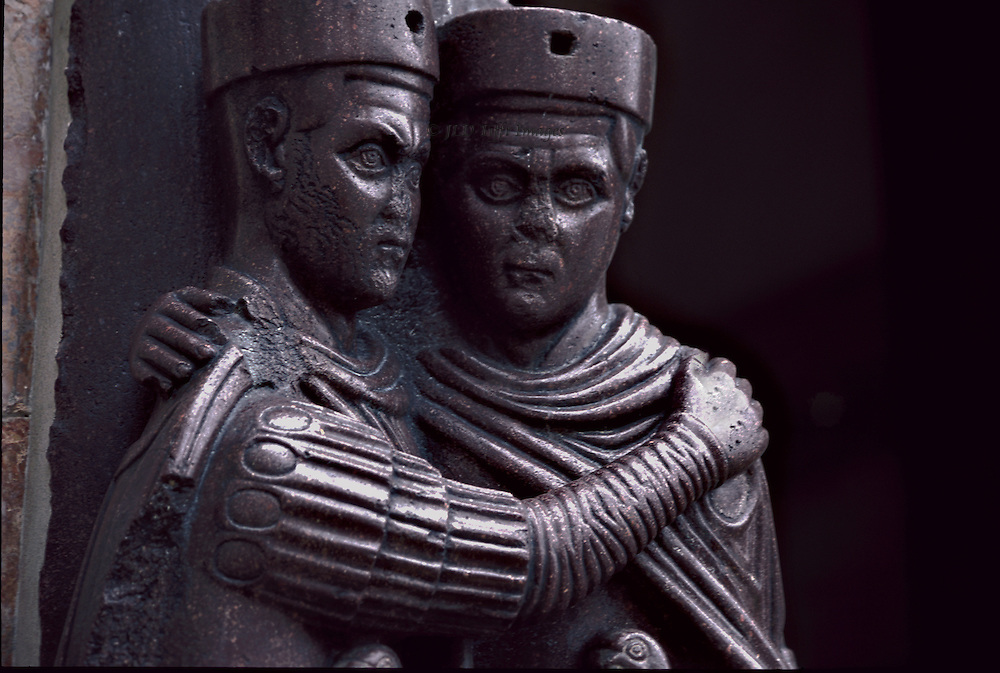 The Tetrarchs, porphyry sculptures on wall of San Marco, Venice. Close up of two heads and arms, the facial expression of each a blank stare.  Their posture of an embrace was meant to convey that the four emperors would work as one.   The sculpture was taken from Constantinople during the 4th Crusade, in 1204, and installed on the southwest corner of the cathedral.