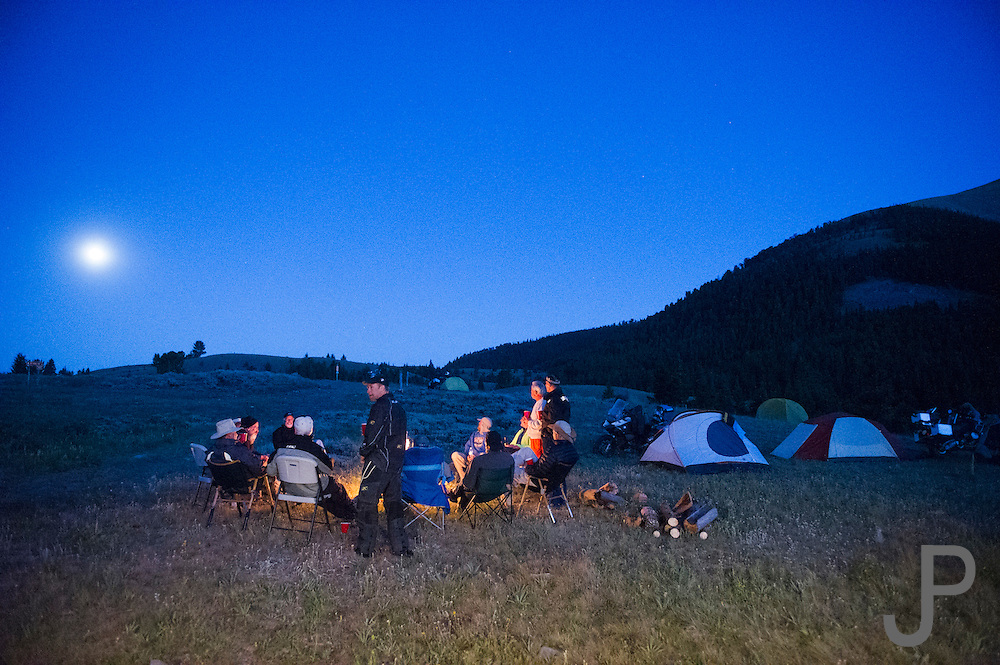 the moon is rising in the background as campers sit around the campfire.