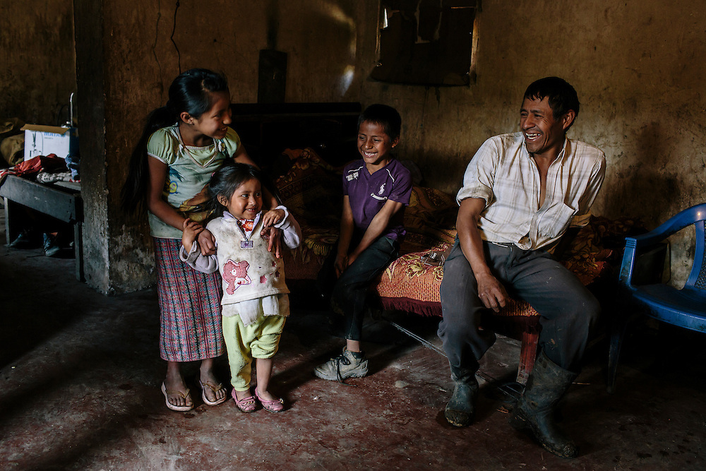 Santos Manuel Luxpu sits with his family at his home in San Juan Cotzal. Luxpu was one of the nearly 80 percent of farmers making the journey to the coast and neighboring countries to slash sugar cane. Now Luxpu is home year round after switching to running his own farm in the highlands of Guatemala and using a system developed by ADIAP, a partner of USAID, to diversify his crops and plant crops that can be sold off more quickly. Luxpu says he makes more money now, because he doesn't have to pay for the transportation to the coast to or the room and board while there for six months a year. The father of five also said he gets to be around his children and check on them in school.