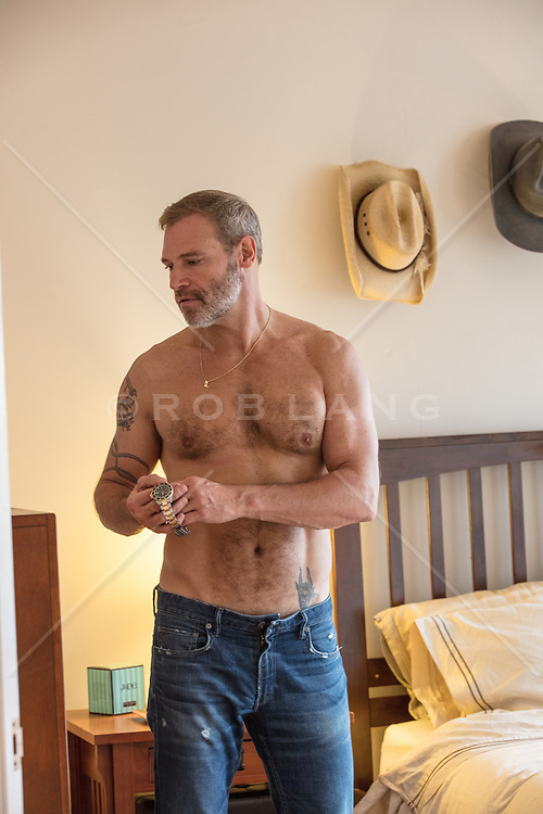 shirtless man holding a watch in a bedroom
