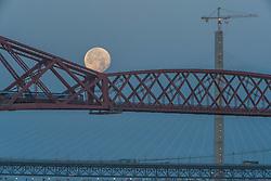 The setting Super-moon behind the Forth Bridge near to Edinburgh