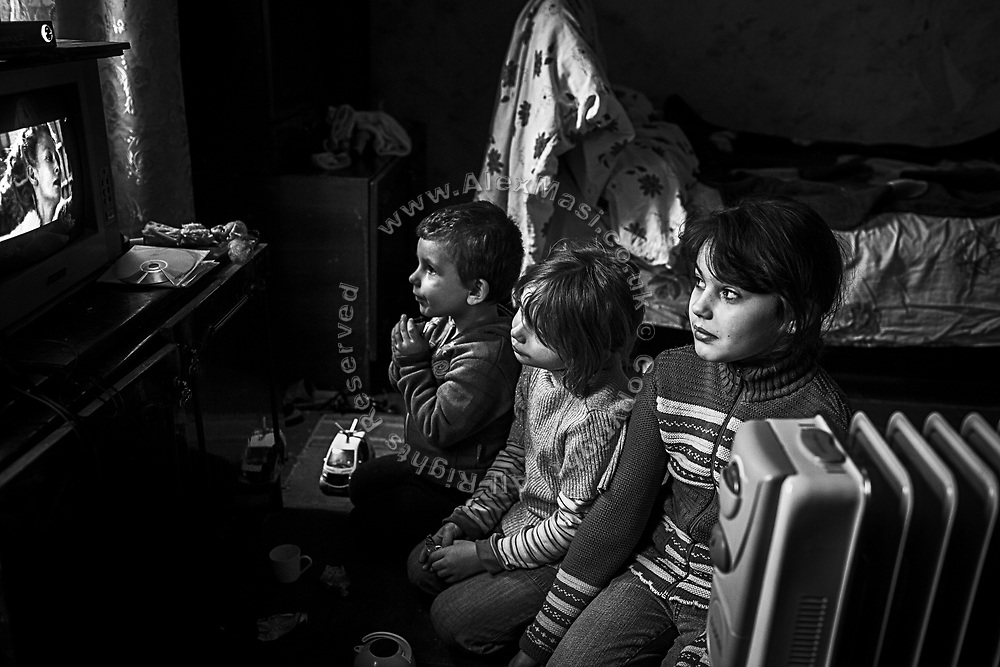 (right to left) Lisa, 9, Nastya, 5 and Daniel Shupertiak, 3, are sitting on the floor of their home while watching a Christian adventure movie, in the town of Popasna, near the frontline in eastern Ukraine.