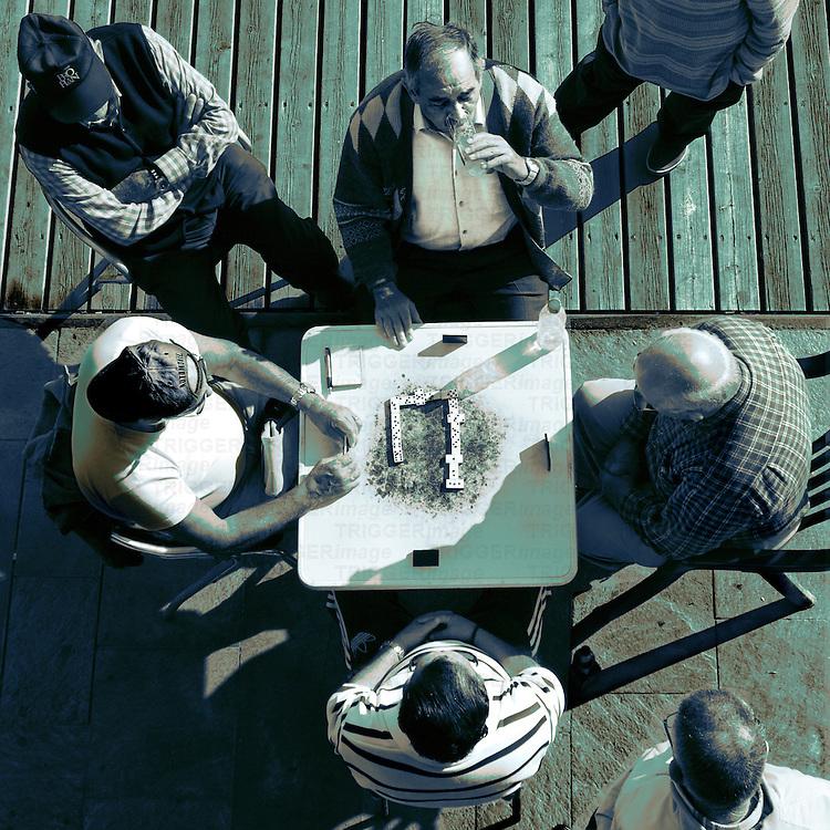 Looking down at men playing dominoes