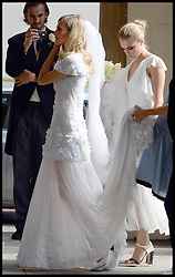 Cara Delevingne holds her sisters dress as they arrive at  Poppy's wedding to James Cook at St.Paul's Church in Knightsbridge, London,  Friday, 16th May 2014. Picture by Stephen Lock / i-Images